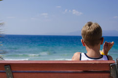 Boy sitting on a bench looking to sea horizon Royalty Free Stock Image