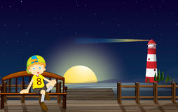 A boy sitting at the bench in the middle of the night Stock Image