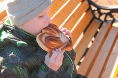 Boy is sitting on a bench in the park in the spring and eating a bun with sugar. Side view. stock photos