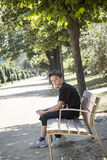 Boy sitting on a bench in a park Royalty Free Stock Photos