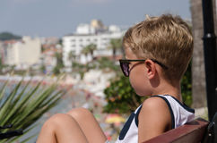 Boy sitting on a bench in sun glasses Stock Image
