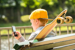 Boy Sitting On Bench Using Mobile Phone Stock Photography