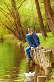 Boy sitting with bended knee near the pond. And white paper boat on the water in beautiful forest landscape Royalty Free Stock Photo