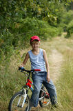 Boy sitting on bicycle. Young blond boy wearing a cap sitting on his bike, posing Royalty Free Stock Photography