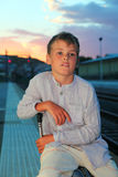 Boy sitting on big bag on platform of railway Stock Photos