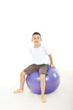 Boy sitting on big ball Royalty Free Stock Images