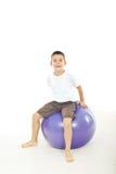 Boy sitting on big ball. I against white background Royalty Free Stock Images
