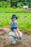 Boy sitting on a big mushroom Stock Photos