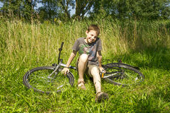 Boy sitting on the bike in grass. The boy sitting on the bike in grass Stock Photos