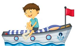 A boy sitting in the boat fixing his sock Stock Photo