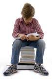 Boy sitting on books on white background Stock Photo