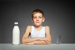 Boy sitting with bottle of milk Royalty Free Stock Photography