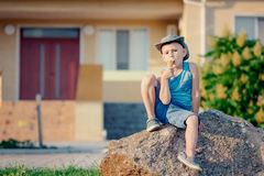 Boy Sitting on Boulder Eating Ice Cream Cone Stock Photography