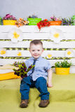 Boy sitting with a bouquet of flowers in a denim suit Stock Photo