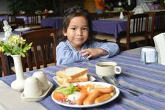 Boy sitting at breakfast table Stock Images