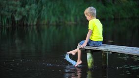 Boy sitting on bridge at pool