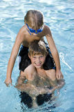 Boy sitting on brother's shoulders in pool Stock Image