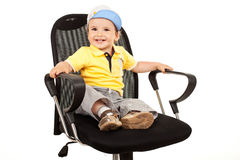 Boy sitting on a business chair Royalty Free Stock Photography