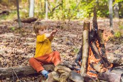 The boy is sitting at the camp fire Stock Image