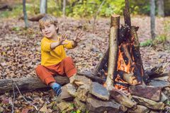 The boy is sitting at the camp fire Stock Images
