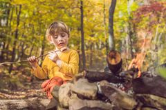 The boy is sitting at the camp fire and eating a fried sausage Stock Images