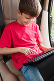 Boy is sitting in a car and playing with ipad. Stock Photography