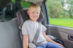 Boy sitting in a car in safety chair Royalty Free Stock Photos
