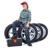 Boy sitting on car tires Stock Image