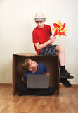 Boy sitting in a cardboard box with a laptop, boy sitting on the cardboard with a colorful windmill paper Stock Images