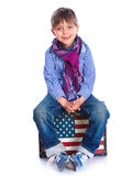 Boy sitting on a case Stock Photography