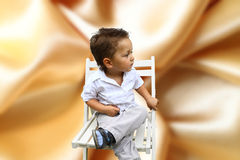 Boy sitting on a chair. Against the backdrop of the beautiful wallpaper and carefully looking away Stock Photo