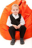 Boy sitting on a chair Stock Images