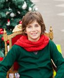 Boy Sitting On Chair Against Christmas Tree Stock Images