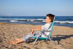 Boy sitting on chair at beach Royalty Free Stock Photography