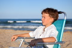 Boy sitting on chair at beach Royalty Free Stock Photos