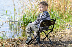 Boy Sitting in Chair and Fishing Amongst the Reeds Stock Image
