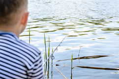Boy Sitting in Chair and Fishing Amongst the Reeds Royalty Free Stock Photo
