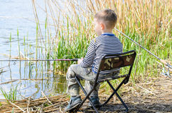 Boy Sitting in Chair and Fishing Amongst the Reeds Stock Photos