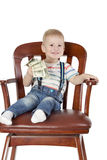 Boy sitting in chair and holding dollars Royalty Free Stock Photo