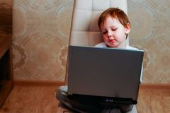 The boy is sitting on a chair and is holding a laptop royalty free stock photography