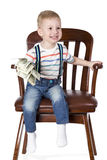 Boy sitting in chair and holding money Royalty Free Stock Photo