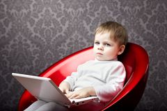Boy sitting in a chair with a laptop Stock Photo