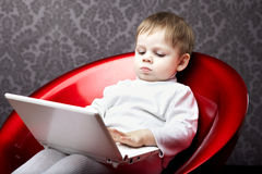 Boy sitting in a chair with a laptop Stock Photography