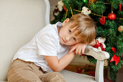 Boy sitting in a chair and sad at Christmas Stock Photos