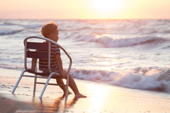 Boy sitting on the chair by sea Royalty Free Stock Photo