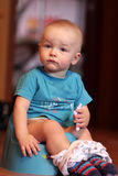 Boy is sitting on chamberpot. The boy is sitting on chamberpot at home royalty free stock photography