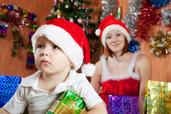 Boy sitting with  Christmas gift. Little boy sitting with  Christmas gift at home Royalty Free Stock Images