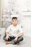 Boy sitting at christmas tree with gifts around Stock Images
