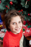 Boy sitting beside the christmas tree Royalty Free Stock Images