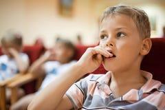 Boy sitting in cinema armchair Stock Image